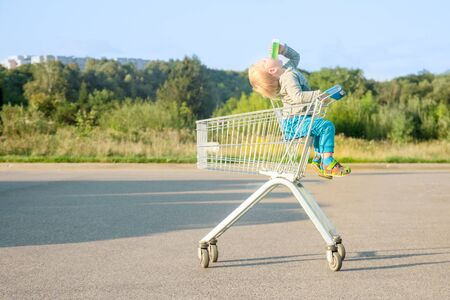 child boy blond in blue pants sits in a metal grocery trolley from a supermarket drinks juice throwing his head on an asphalt surface in the summer against a background of green plants