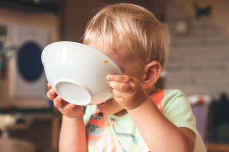 blond kid boy, very hungry eats and holds a plate with both hands, is covered with a plate