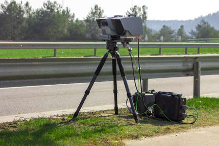 Vilnius, Lithuania - March 28, 2020: A mobile camera on a tripod standing near the road measures the speed of a passing vehicle