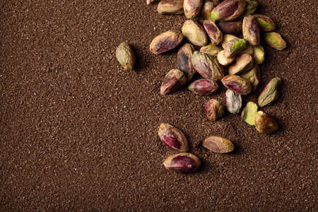 Pistachio nuts on brown textured sand background