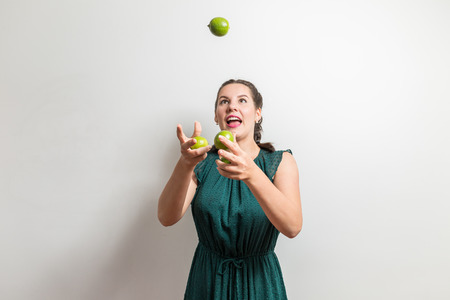 Funny girl tries to juggle with fruits Stockfoto