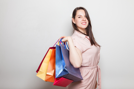 Pretty smiling female and color shopping present bags Stock Photo