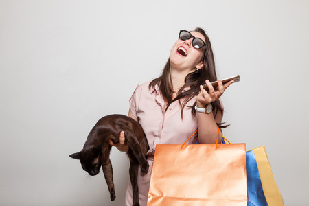 Powerful laughing woman screams holding cat and bags Stock Photo