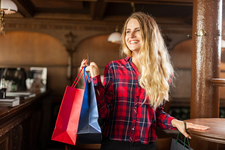 Attractive young woman is smiling and holding bags full of stuff she bought by cash in gift store