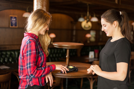 Smiling waiter waits when the credit card payment is made in cafe