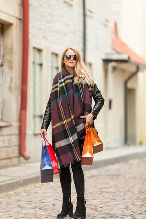 Stylish blond walks to fashion store Stock Photo
