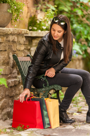 Cute brunette girls checking her shopping bags Stock Photo