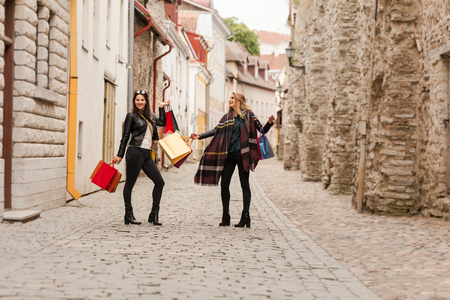 Smiling girls are dancing on the streets because of the big black friday sales