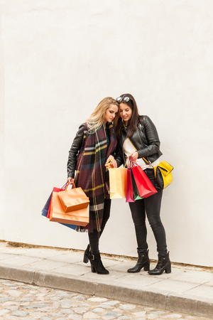 Two gorgeous girls look inside shopping bags on a street and get surprized