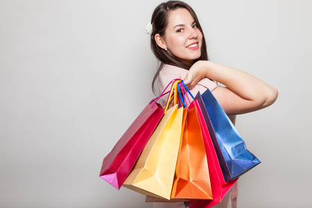 Adorable brunette shows many shopping bags from mall