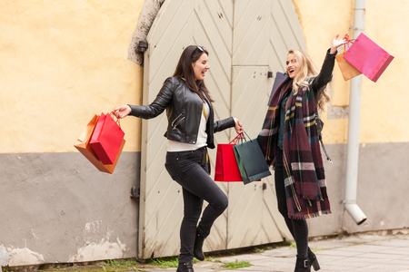 Crazy deals at fashion boutique stores. Girls are excited with shopping bags in hands