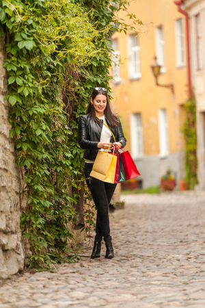Pretty brunette young girl waits for the shop to open its doors in front of a wall with leaves with big bags Stock Photo