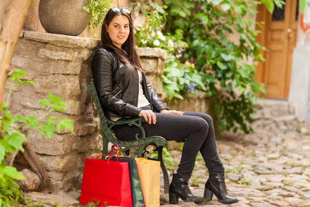 Pretty woman sits in a park with bags