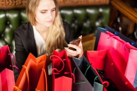 Blond woman sitting in a cafe uses smartphone to order products online from internet shop Stock Photo
