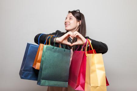 Cute teenage girl shows heart holding bags