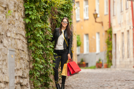 Modern teenager in a leather jacket and glasses stand on a corner of a street Stock Photo