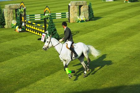 Rider prepares for next obstacle in a horse jumping competition. photo