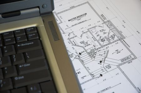 Laptop computer and residential blueprints. photo