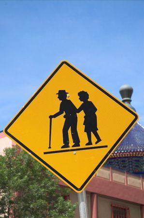 A senior crossing warning sign in Calgarys china town. Banco de Imagens