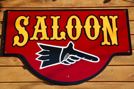 An old saloon sign attached to a western building. Imagens