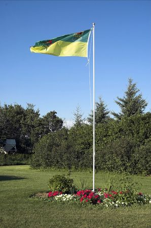 Green and yellow Saskatchewan flag flutters in the breeze on a Saskatchewan farm. Stock Photo - 3062436