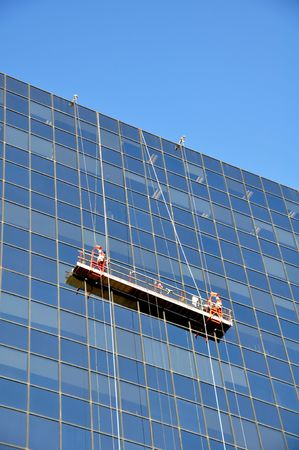 Two window cleaners in a gondola cleaning the windows of a corporate office skyscraper.Two window cleaners in a gondola cleaning the windows of a corporate office skyscraper.