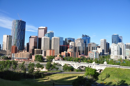 Skyscrapers towering over Calgary Alberta Canada with Bow river and Centre Street bridge in foreground.  Stock Photo