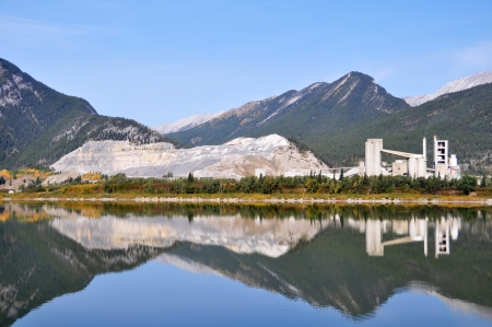 Cement Plant located in Exshaw Alberta in the Rocky mountains close to the entrance to Banff National Park  The large scar along the left side of the image indicates where rock has been carved from the mountain for the manufacture of cement Banco de Imagens - 15484459