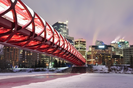 A Calgary pedestrian bridge accross with Bow River in winter with skyscrapers in background   photo