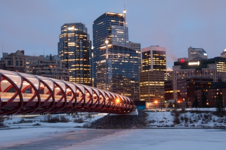 coulorful: A Calgary pedestrian bridge accross with Bow River in winter with skyscrapers in background
