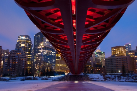 coulorful: A Calgary pedestrian bridge across with Bow River in winter with skyscrapers in background