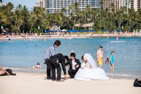 newlyweds on crowded Waikiki Beach on June 22, 2013 in Oahu. Waikiki beach, best known for white sand and surfing, is popular for weddings.