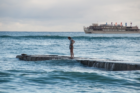 Surfer girl at sunset watches as a large cruise ship passes Waikiki beach in Oahu, Hawaii.