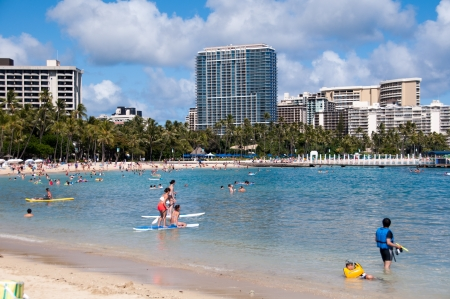 OAHU, HI - Tourist sunbathing and surfing on Waikiki beach June 26, 2013 in Oahu. Waikiki beach is beachfront neighborhood of Honolulu, best known for white sand and surfing. Editorial