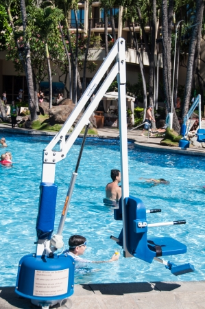ADA standard disabled person pool lift used at swimming pools in order to lower a person into the water. This device is located at the Hawaiian Hilton in Waikiki and helps make the resort accessible to all. Editorial