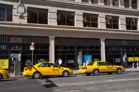CALGARY, CANADA - SEPT 11  Yellow cabs line up for fares in Calgary, Alberta on September 11, 2013 in Calgary, Alberta  This cab stand is located in downtown Calgary and office buildings are behind  新闻类图片