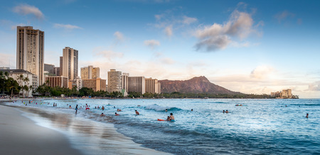 Tourists on the beach front at sunset on Waikiki beach in Oahu