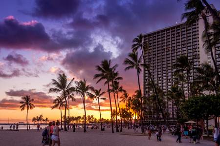 OAHU, HI - JUNE 26 -Waikiki Beach at the Hawaiian Hilton Village at sunset on June 26, 2013  People visible on beach  The Hawaiian Hilton Village is very popular with families traveling to Hawaii