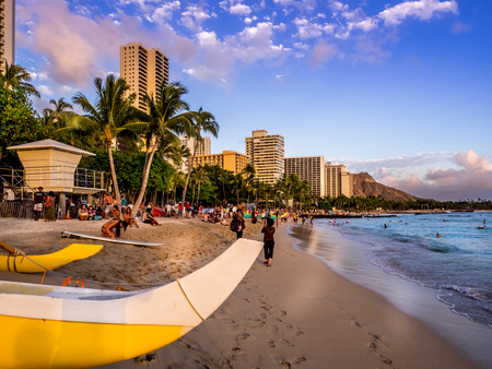 Tourists on the beach front at sunset on Waikiki beach April 27, 2014 in Oahu  Waikiki beach is beachfront neighborhood of Honolulu, best known for white sand and surfing