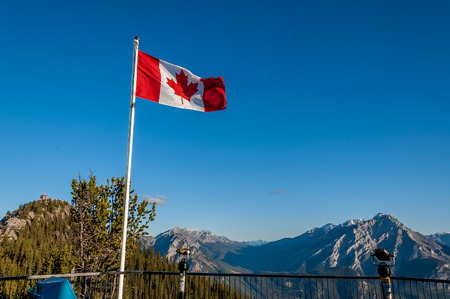 Canadian flag flutters in the wind on top of Sulpher Mountain in Banff.