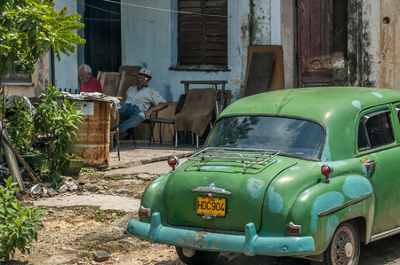 shadowed: Old men rest in shadowed area on June 30, 2005 in Havana, Cuba. Havana is very hot in summer. An old vintage car is visible in the foreground. Editorial