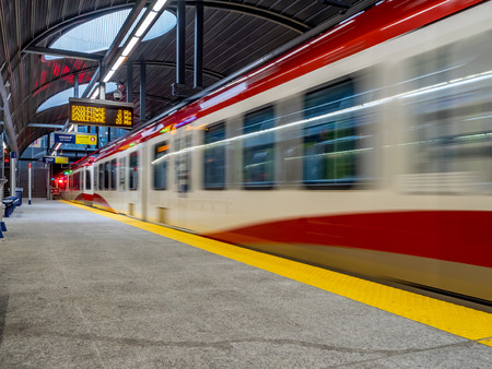 co2 emissions: The Ctrain speeding into Westbrook stations on May 24 2015 in Calgary Alberta. The Ctrain is Calgarys light rail transit vehicle and moves over 300000 people a day.