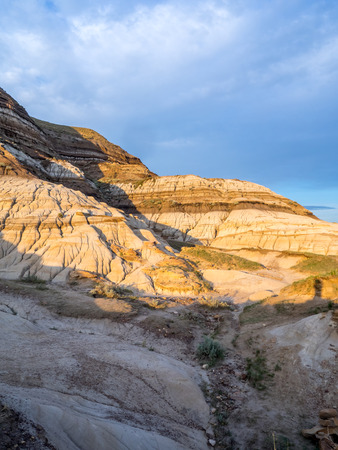 bathed: Badlands bathed in the warm light of a summer sunset near drumheller in Alberta Canada.
