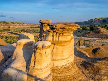 badland: Hoodoos bathed in the warm light of a summer sunset at Drumheller Alberta Canada.