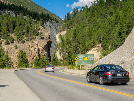 radium: KOOTENAY NATIONAL PARK, CANADA - AUG 8:Cars pass an avalanche warning sign in Kootenay National Park on August 8, 2015 in British Columbia, Canada.