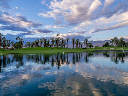 Beautiful sunrise over a water feature on a golf course in Palm Desert California. Imagens