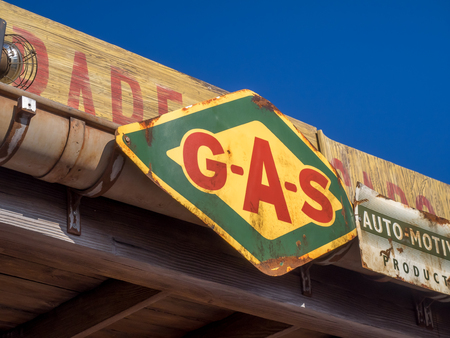 Vintage gas sign on old building. Imagens