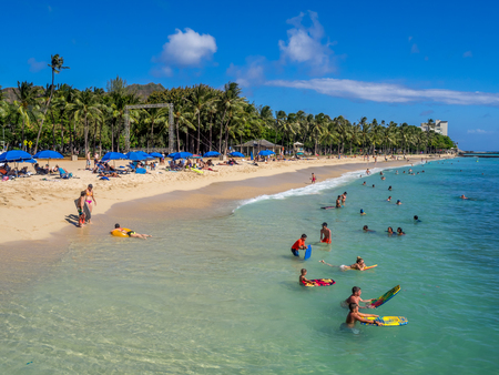 HONOLULU, USA - AUG 4: Sun lovers on Waikiki beach on August 4, 2016 in Honolulu, Usa. Waikiki beach is neighborhood of Honolulu, best known for white sand and surfing. Editorial
