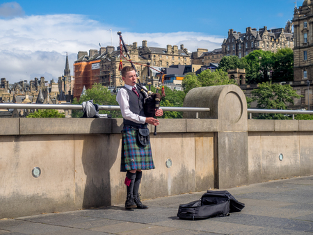 EDINBURGH, SCOTLAND - JULY 26: Unidentified Bagpiper playing music with bagpipes along the Mound on July 26, 2017 in Edinburgh Scotland. There are many bagpipers busking and entertaining tourists! Editorial
