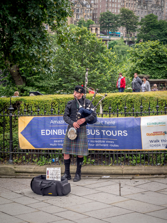 EDINBURGH SCOTLAND - JULY 28: A Scotsman wearing traditional Scottish outfit playing the bagpipes along Princes Street on July 28, 2017 in Edinburgh, Scotland. There are many pipers busking.